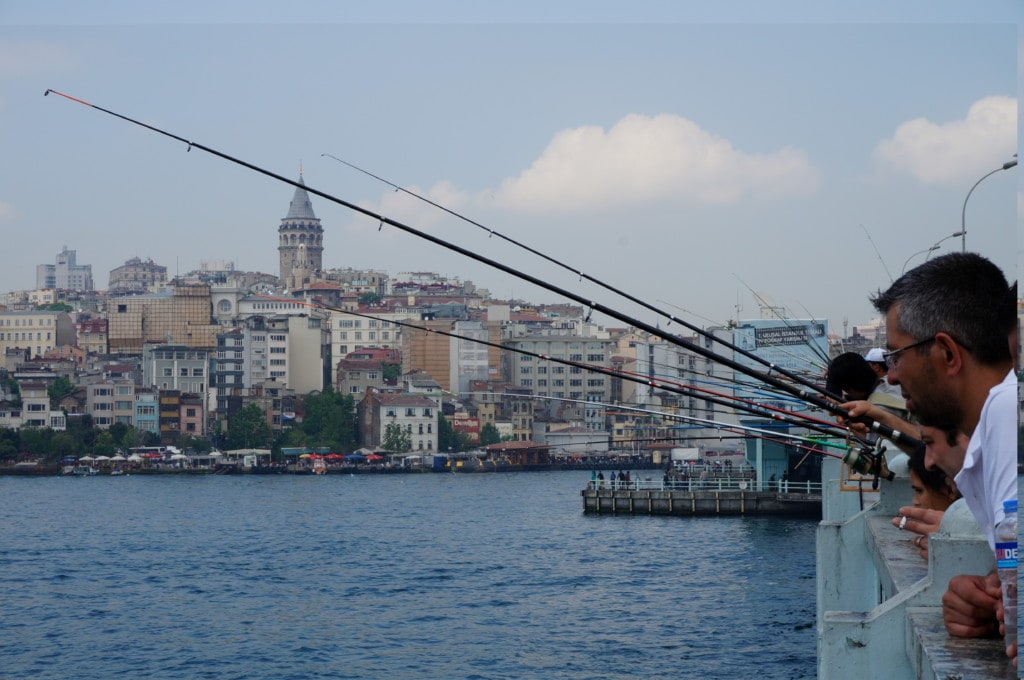 Galata Bridge is a popular spot for locals to fish, you can see Galata Tower in the distance